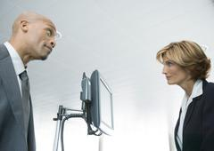 Businessman and female airline attendant staring at each other Stock Photos