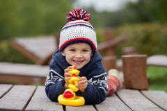 Adorable little boy, playing with rubber ducks outside on an autumn day Stock Photos