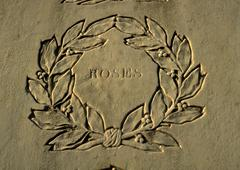 Stock Photo of Roses typography engraved in stone surrounded by engraved wreath.