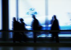 People walking past windows, silhouette, defocused - stock photo