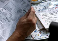 Man reading newspaper at table, close up of paper. Stock Photos