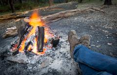 warming feet by campfire - stock photo