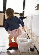 Little girl next to children's toilet with panties around ankles, rear view, - stock photo