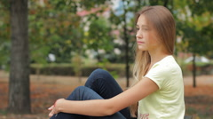 Sad And Depressed Teenage Girl Sitting On Bench In City Park Deep In Thought HD Stock Footage