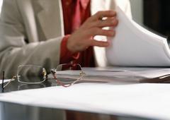 Man doing paperwork, focus on eye glasses on desk - stock photo