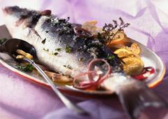 Whole cooked fish with citrus fruit and herbs on dish, close-up Stock Photos