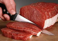 Fingers holding knife, slicing raw beef fillets, close-up - stock photo