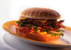 Cheeseburger with tomatoes, lettuce, and bacon on sesame seed bun, close-up Stock Photos