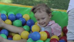 The girl is awash in colorful balls. Childhood, child, day Stock Footage