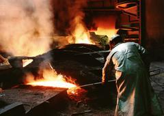 Man bending forward, working in blast furnace, rear view Stock Photos