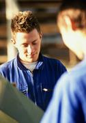 Men in coveralls, looking down - stock photo