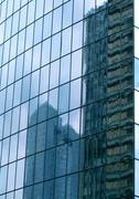 Buildings reflected in window panes of skyscraper - stock photo