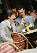 Two businessmen sitting at cafe terrace, looking at laptop computer Stock Photos