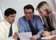 Two businessmen and a businesswoman examining document Stock Photos