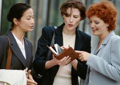 Three businesswomen side by side, one holding agenda Stock Photos