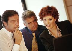 Two businessmen and a businesswoman side by side Stock Photos