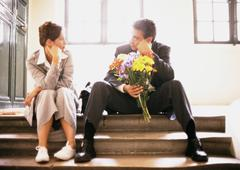 Man and woman sitting on steps, looking at each other, man holding bouquet Stock Photos
