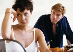 Woman sitting, elbow on back of chair, hand against head, man leaning toward her - stock photo