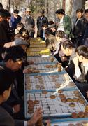 China, Xinjiang, Urumqi, men playing xiangqi, weiqi, outdoors - stock photo