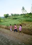 China, Guangxi Autonomous Region, children walking single file along dirt road - stock photo