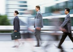 Three business people walking with briefcases, side view, blurred - stock photo