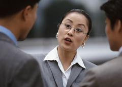 Businesswoman speaking with two male associates Stock Photos