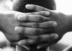 Man's hands clasped behind head, close-up, b&w Stock Photos