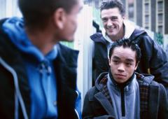 Three young men outside, building in background Stock Photos