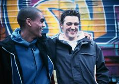 Stock Photo of Two young men, one with arm around the other, smiling