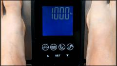 Feet standing on weight scale with measuring 100kg Stock Footage
