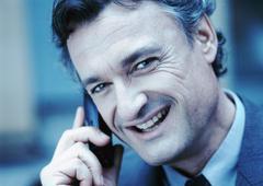 Businessman using cellular phone, smiling at camera, close-up, cool toned. Stock Photos