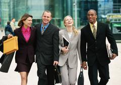 Group of business people walking together outside, three quarter length, front - stock photo