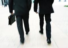 Businessmen walking together, lower section, blurred. Stock Photos