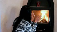 Young woman with tea by the fire Stock Footage