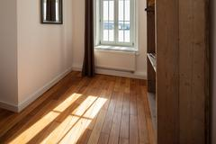sunlight shining onto a wooden parquet floor - stock photo