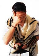 Jewish man wearing Tefillin and Tallith for prayer, covering face with hand, - stock photo