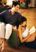 Man sitting backwards on chair and pregnant woman sitting on floor, reading and Stock Photos