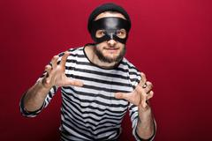 Masked criminal ready to fight. Portrait on red background Stock Photos