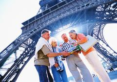 France, Paris, group of mature tourists examining a map in front of Eiffel Stock Photos