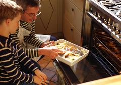 Man and child putting casserole in oven Stock Photos