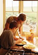 Man and child making apple pie - stock photo