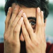 Young man with hands over face, looking through fingers with one eye, close-up Stock Photos
