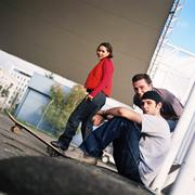 Three young people, one with skateboard, side view, portrait Stock Photos