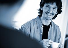 Man holding teacup, smiling, at second person in foreground, blurred Stock Photos