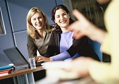 Women sitting at laptop computer, smiling, person pointing in foreground, Stock Photos