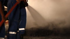 A team of fire fighters hold a hose and put out a house fire Stock Footage