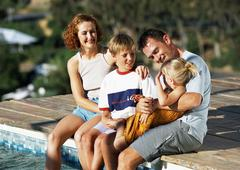 Young family, dressed, sitting on edge of pool. - stock photo