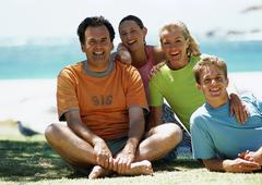 Family sitting on beach, smiling, front view, sea in background, portrait. Stock Photos