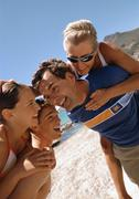 Close-up of two men carrying women on their backs on the beach. - stock photo
