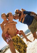 Two men carrying women on backs on the beach. Stock Photos